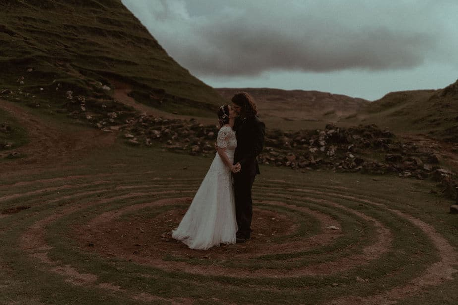 Couple kissing inside circle at Fairy Glen, Isle of Skye.