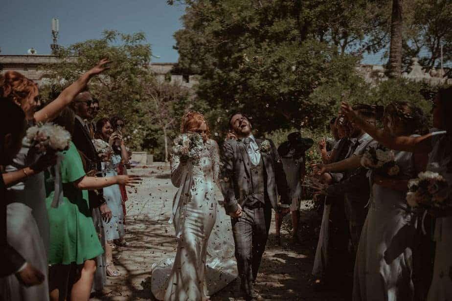 couples walking through guests throwing confetti at Malta Wedding - Villa Bologna Wedding, Malta.