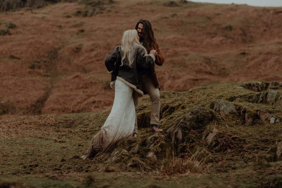 Couple climbing up Blea Tarn after Lake District Wedding