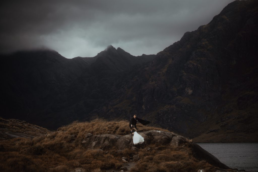 Couple climbing up hill at Loch Coruisk for elopement - Scotland Elopement Guide.