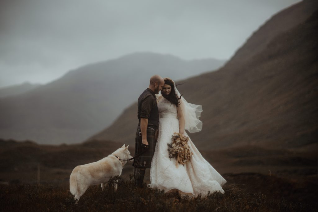 Couple standing with husky during elopement ceremony at Glen Etive, Scotland