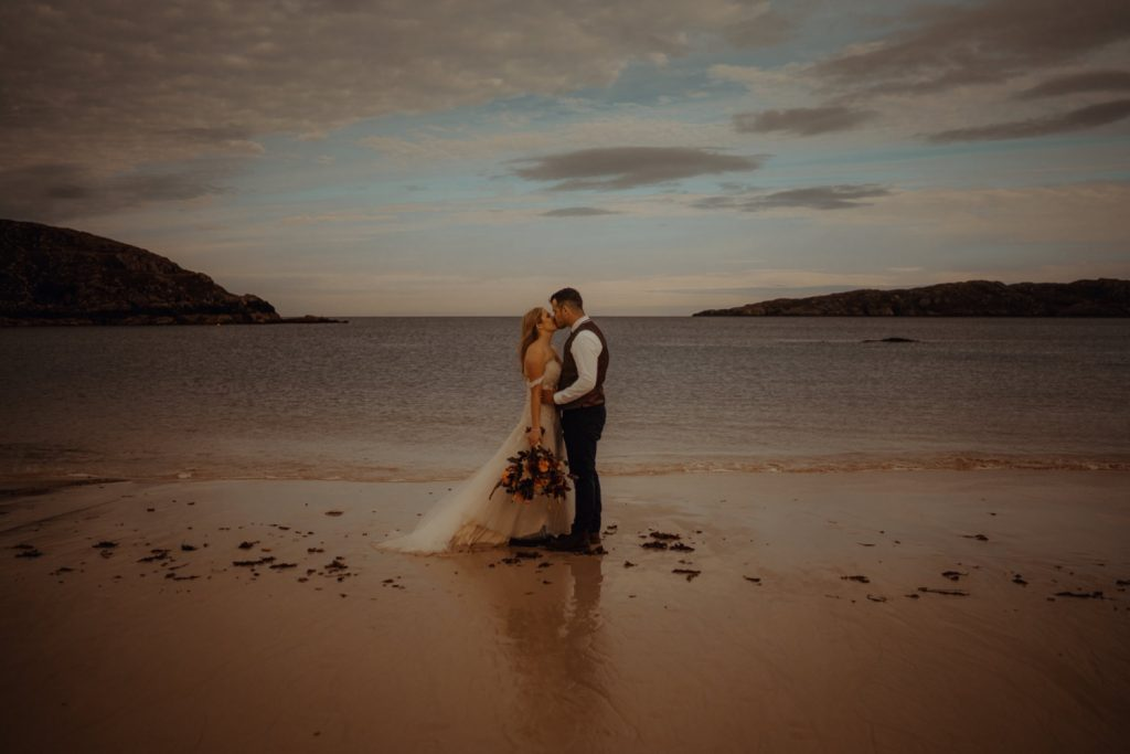 couple kissing at Achmelvich Beach during elopement